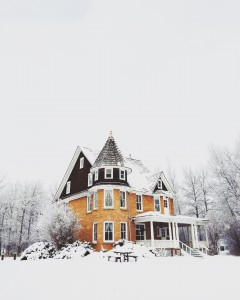 Large yellow Victorian style home with snow on the ground
