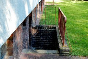 Stairs outside the house leading down into the basement of the home.